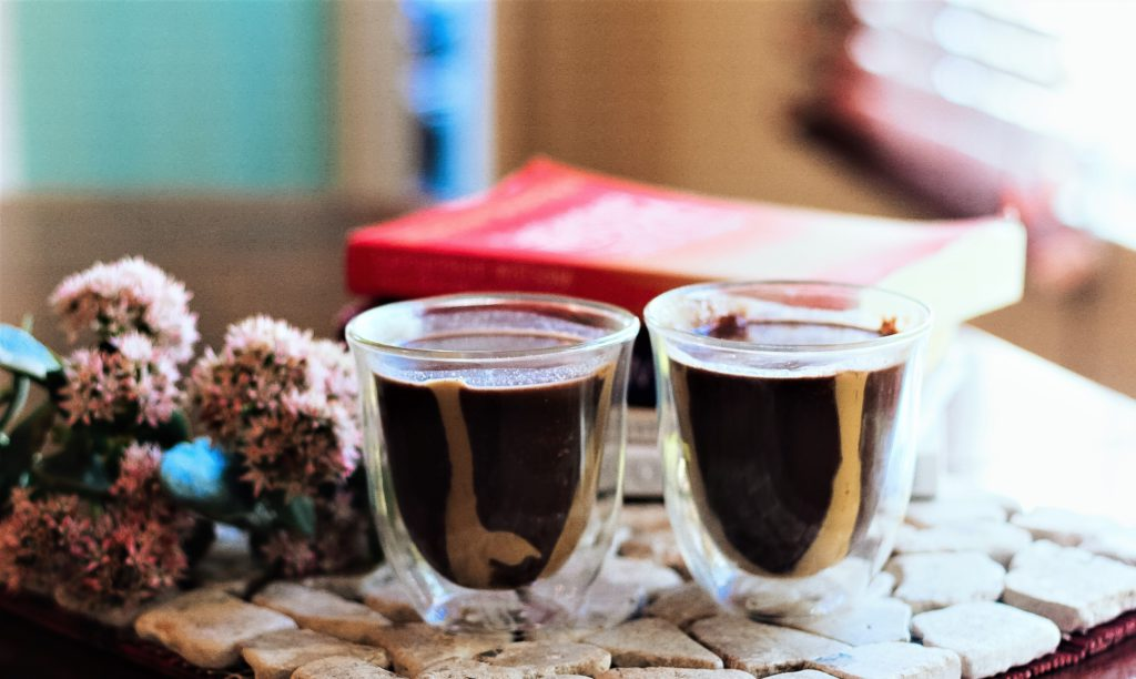 2 transparent glasses with peanut butter hot chocolate in them, standing on a stone place mat with flowers and books next to it.