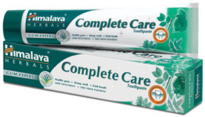A tube of toothpaste sitting on top of its box. The packaging is green and white with menthol leaves.