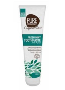 white tube of toothpaste with green and brown writing