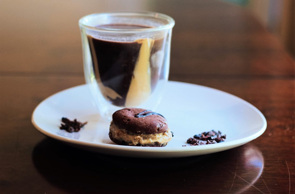 gluten free vegan oreo biscuit with cacao nibs and a glass of hot peanut butter chocolate