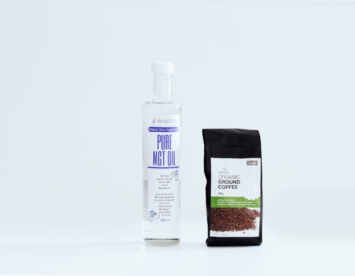 Clean white background with a bottle of transparent MCT oil next to a black bag of organic coffee from wellness wharehouse