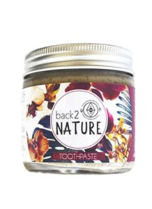 jar of back 2 nature toothpaste, silver lid with a floral purple label.