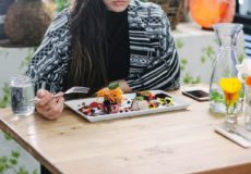woman in black sitting in front of a colourful dessert platter
