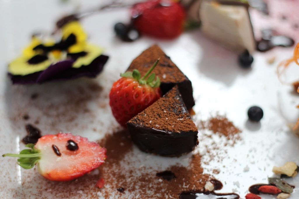 Chocolate ganache sprinkled with cocoa powder and decorated with strawberries